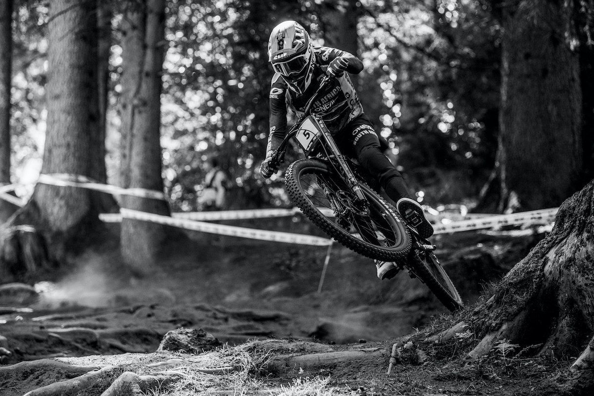 Myriam Nicole produced a perfect run to win the downhill title at the UCI Mountain Bike World Championships in Val di Sole, while South Africa's Greg Minnaar claimed the title for the fourth time.